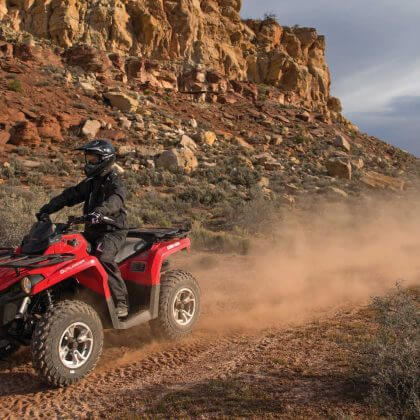 2015.can-am.outlander-l450.red_.front-left.riding.on-dirt