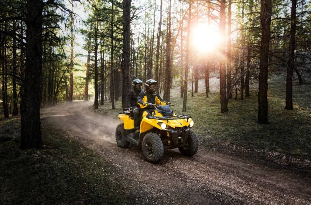 Outlander 570 with two riders driving on dirt road through thick forest