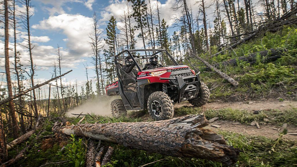 Ranger 570 with two riders driving on dirt road in forest
