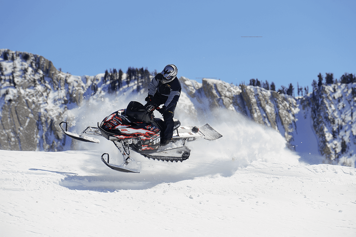 Person jumping a snowmobile with mountains in background