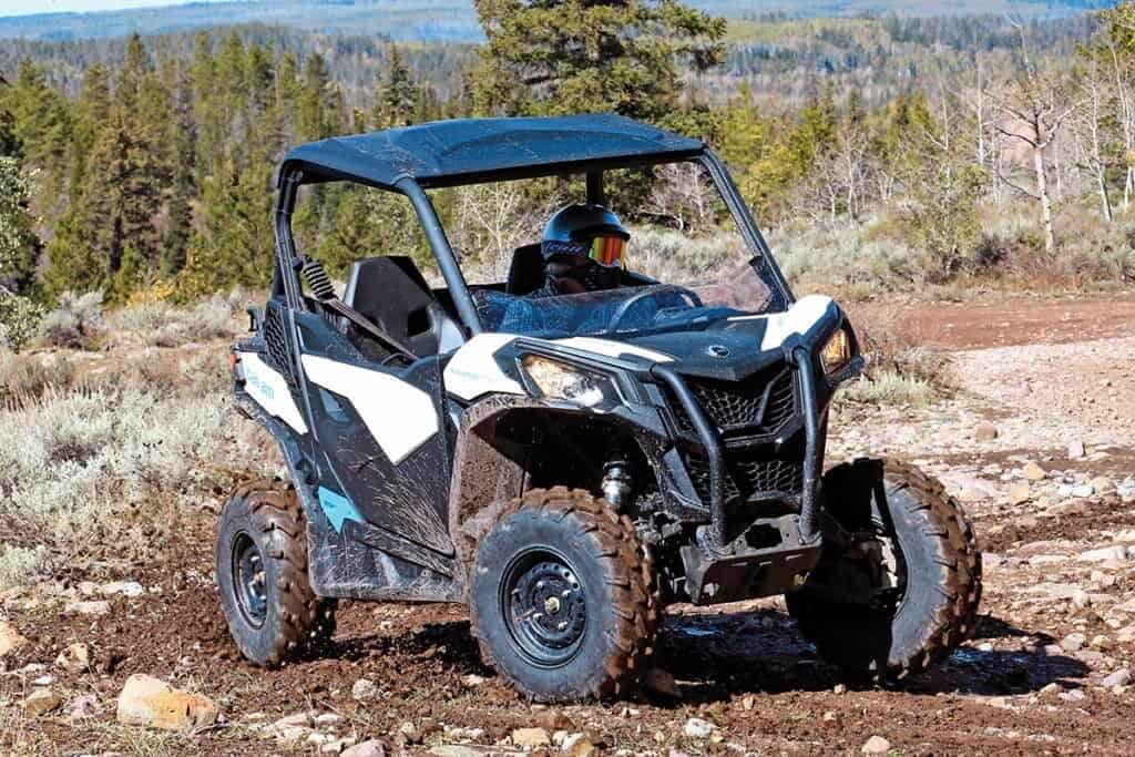 Guy turning sharp on Canam Maverick 800 with forest in the distance
