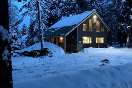Cabin covered in snow with snowmobiles parked outside