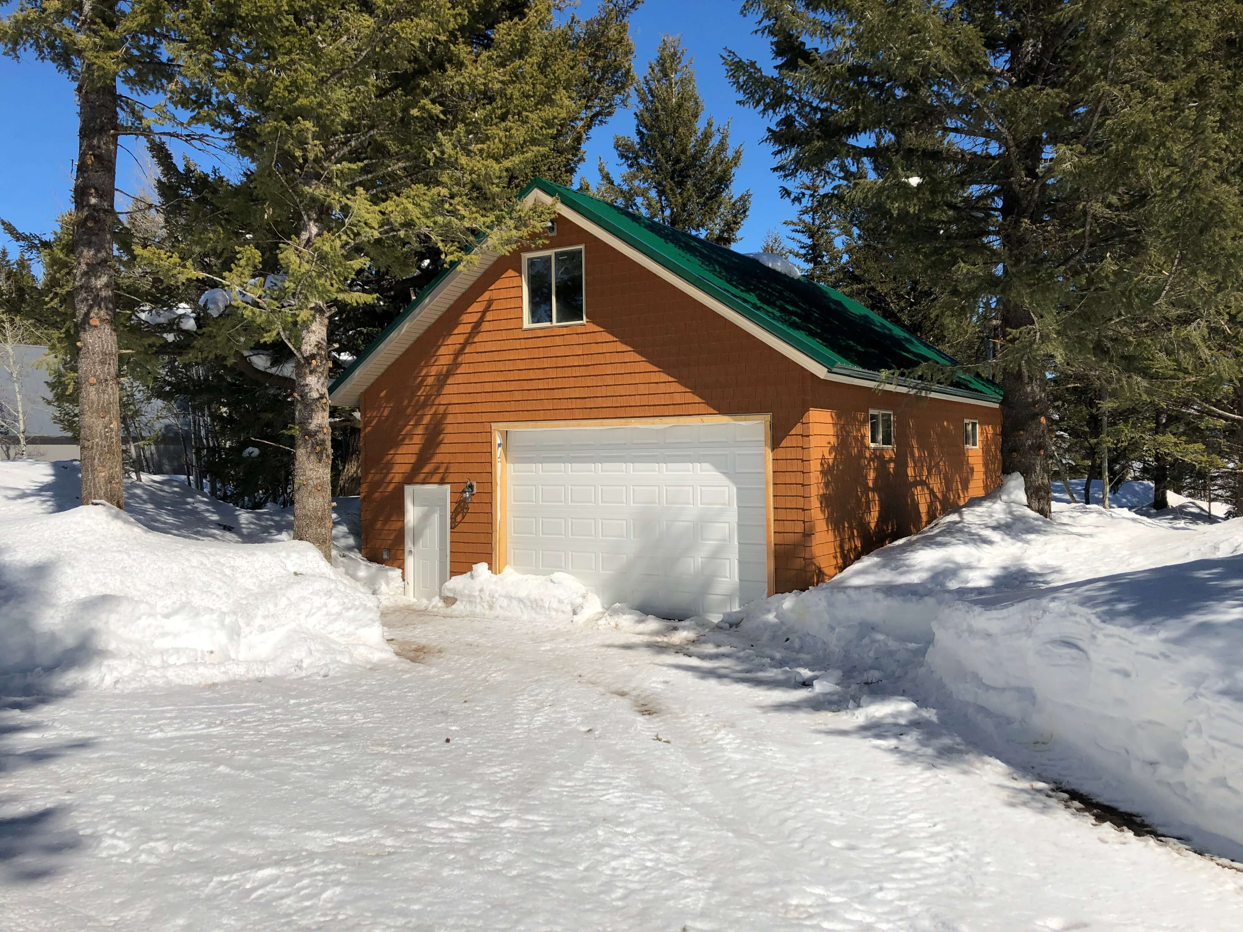 Small cabin loft with garage surrounded by lots of snow