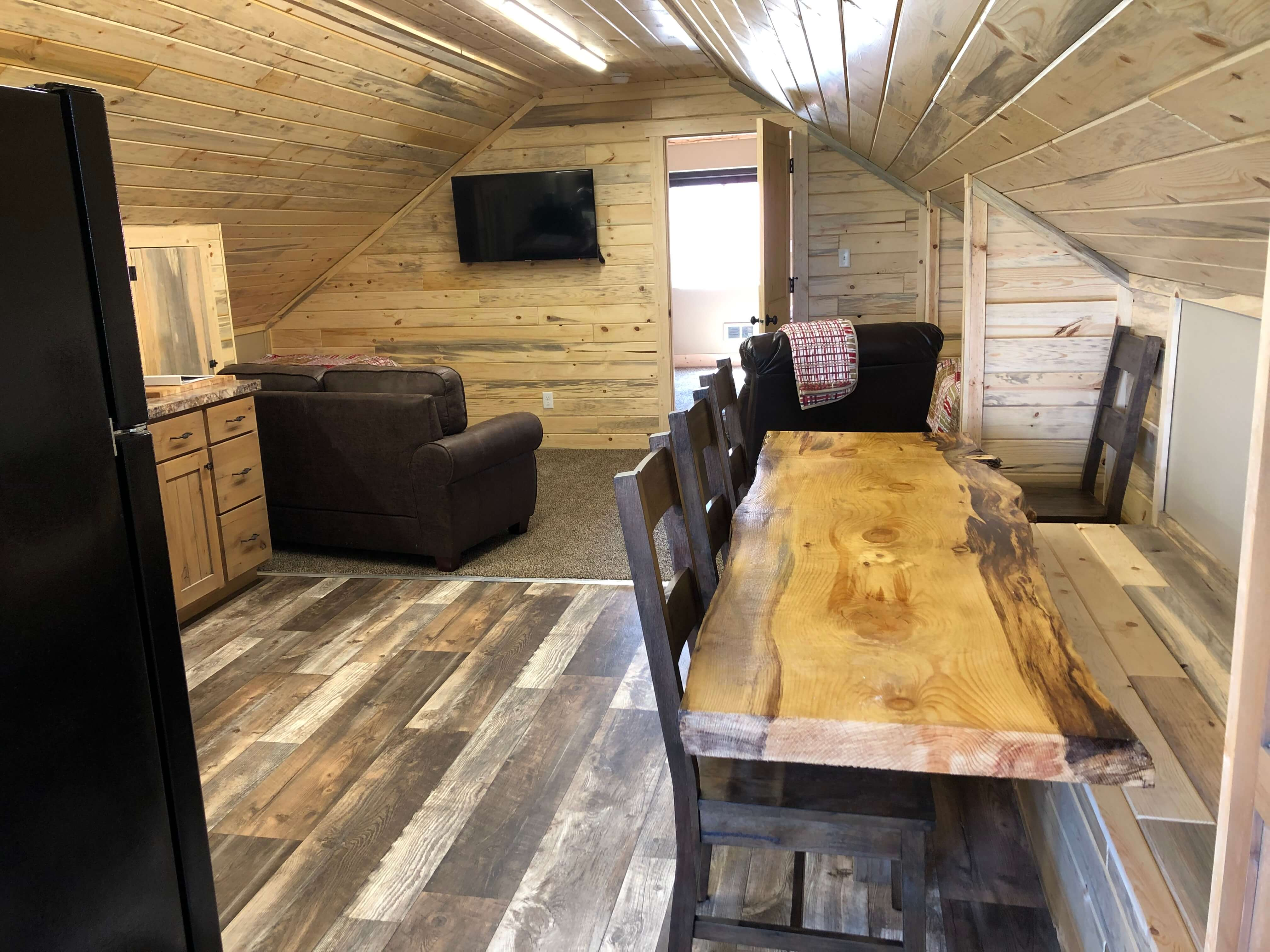 Cabin loft with dinning table, couch, and TV