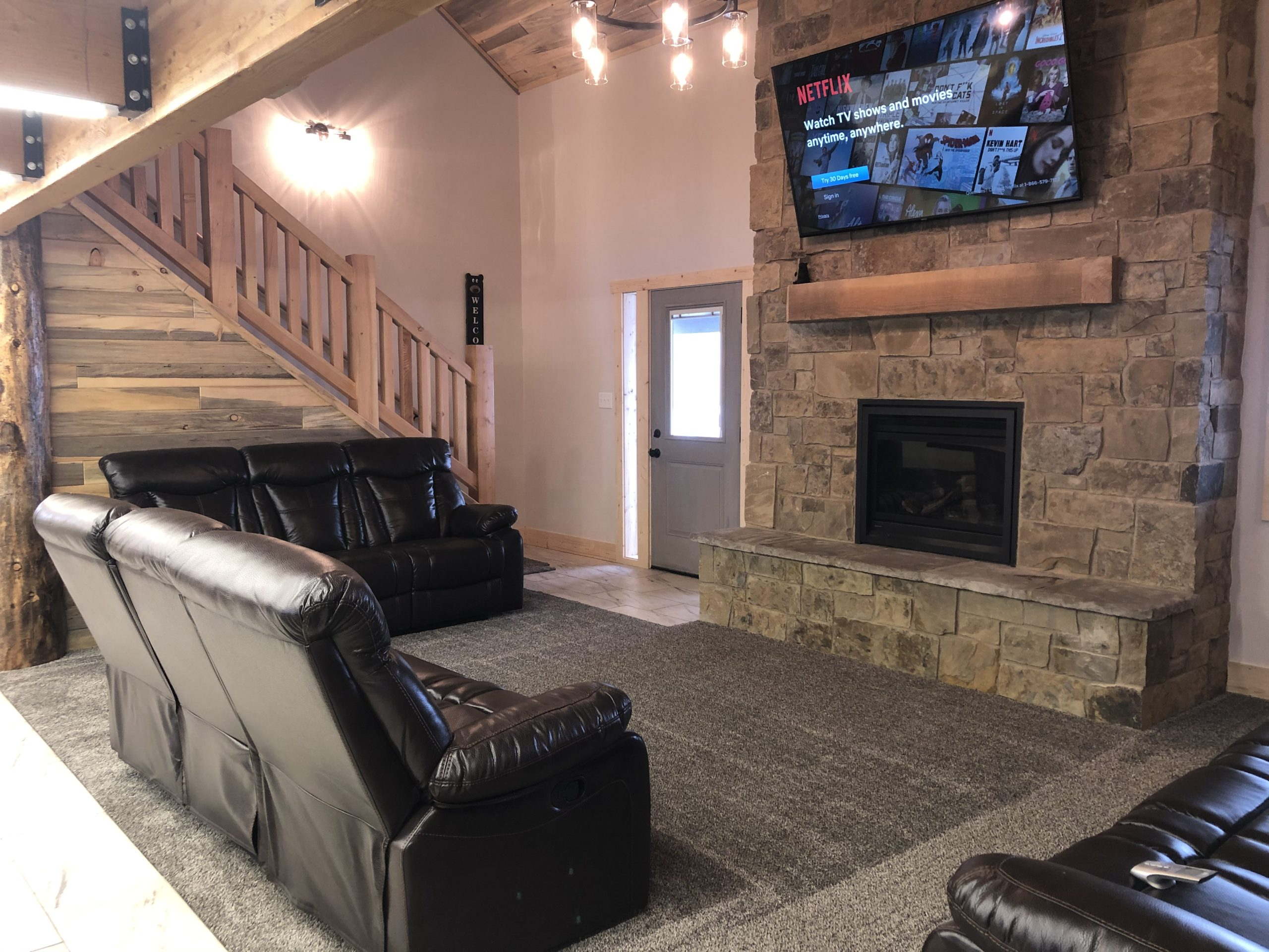 Spacious living room with reclining sofas, gas fireplace, and smart TV